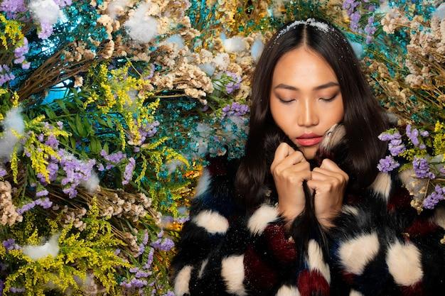 Mooie romantische jonge aziatische vrouw in zwart bont doek in bush verscheidenheid van bloemen poseren op achtergrond verse en gedroogde flora. inspiratie van herfst winter sneeuw parfum, cosmetica concept.