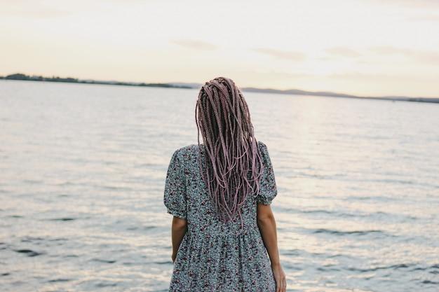 Mooie romantische jonge vrouw met afrikaanse vlechten in jurk op het strand