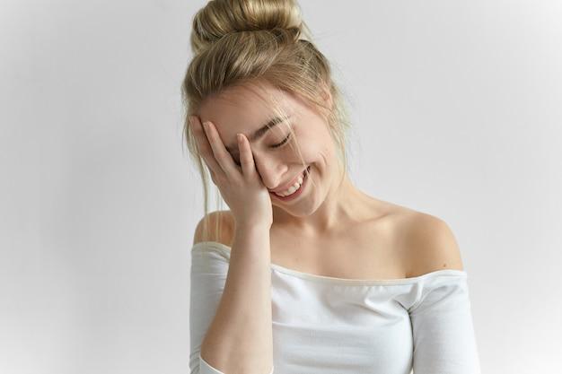 Mooie romantische jonge vrouw met slordig kapsel ogen sluiten en gelukkig glimlachen, haar gezicht bedekken, verlegen zijn. aantrekkelijke vrouw gezicht palm gebaar maken. lichaamstaal