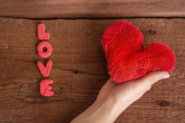 Mooie, romantische kaart voor de dag van de liefhebbers. de hand knijpt in een donzig, rood, zacht hart en daarnaast staat het opschrift 'love'. bovenaanzicht. houten achtergrond