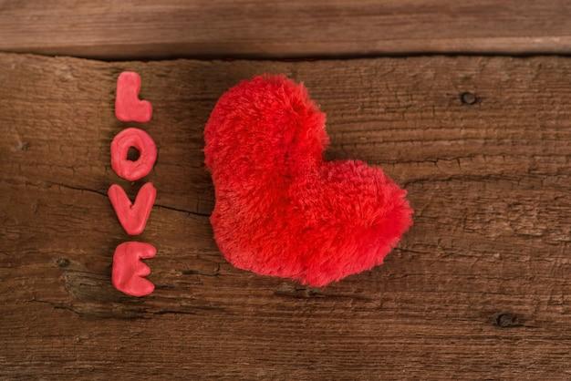 Mooie, romantische kaart voor de dag van de liefhebbers. pluizig, rood, zacht hart en daarnaast staat het opschrift 'liefde'. bovenaanzicht. houten achtergrond
