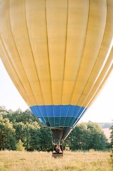 Mooie romantische kaukasische paar verliefd knuffelen in de mand met kleurrijke hete luchtballon tijdens zomer zonsondergang, verloving of huwelijksverjaardag vieren
