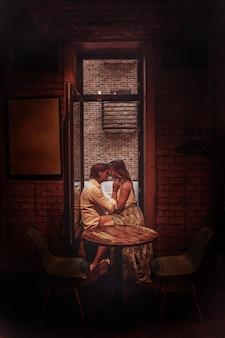 Mooie romantische paar dating in restaurant. jonge geliefden knuffelen en zoenen aan tafel. authentieke love date getint in beige kleuren