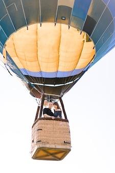 Mooie romantische paar knuffelen in de mand van hete luchtballon, vliegen in zonnige zomeravond
