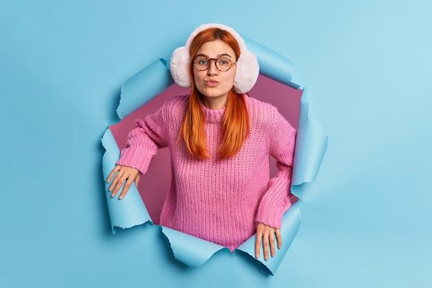 Mooie romantische tienermeisje vouwt lippen wil haar vriendje kussen draagt warme winter oorbeschermers en gebreide trui heeft natuurlijk rood haar.