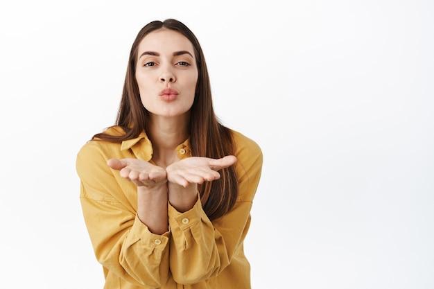 Mooie romantische vrouw die luchtkus aan de voorkant verzendt, handen vasthoudt in de buurt van gebobbelde kussende lippen en mwah naar je blaast, koket en mooi tegen de witte muur