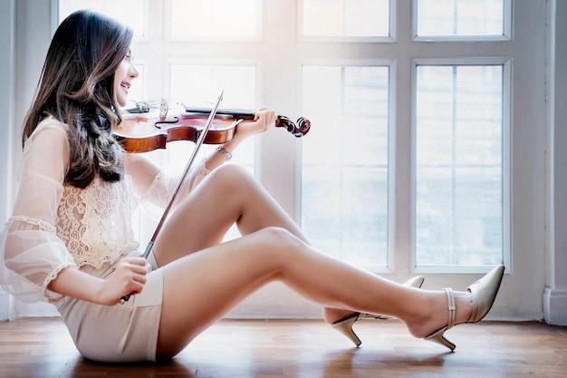 Mooie romantische vrouw met lang haar zitten in de buurt van het venster en spelen op viool