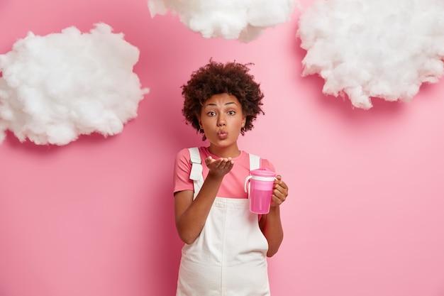 Mooie romantische zwangere vrouw verwacht baby, blaast luchtkus naar echtgenoot, draagt comfortabele kleding, houdt fles met vers water vast, geïsoleerd over roze muur met pluizige wolken erboven. moederschap