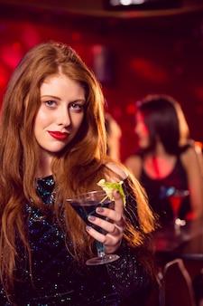 Mooie roodharige die een cocktail drinkt
