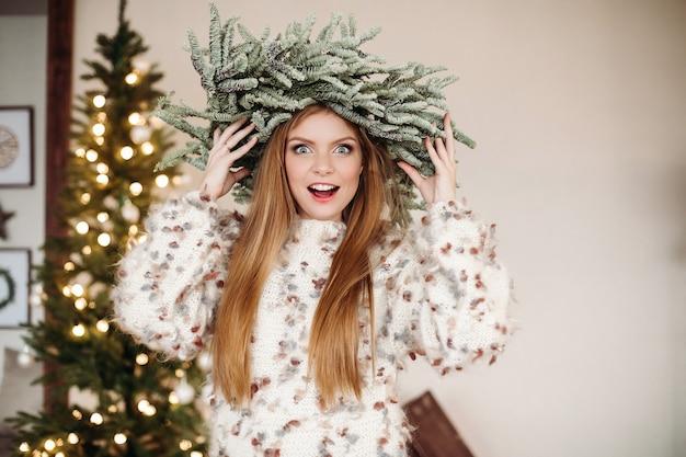 Mooie roodharige draagt een prachtige kerstkrans op het hoofd en kijkt met verbazing naar de camera.