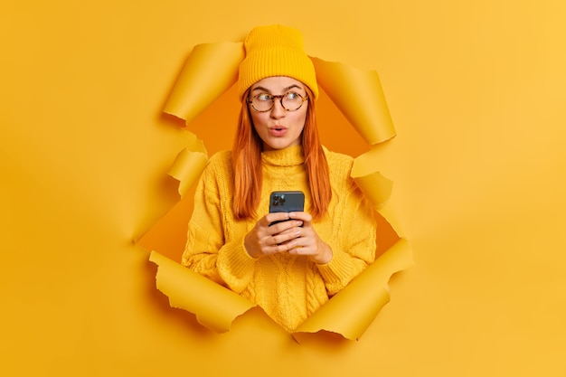 Mooie roodharige duizendjarige vrouw in stijlvolle gele hoed en trui gebruikt moderne mobiele telefoon voor online communicatie kijkt met verwondering opzij.