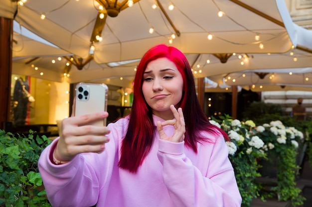 Mooie roodharige influencer blogger meisje in café praten video-oproep met behulp van smartphone met haar abonnees in sociale netwerken.