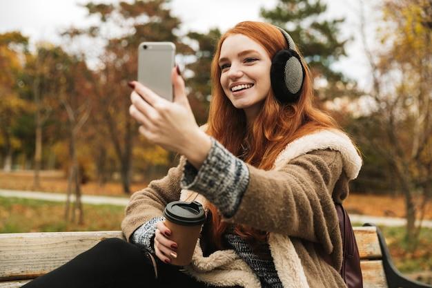 Mooie roodharige jong meisje, luisteren naar muziek met koptelefoon zittend op een bankje, een selfie nemen