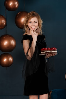 Mooie roodharige jonge lieve meid houdt van snoep taarten en banketbakkersroom.