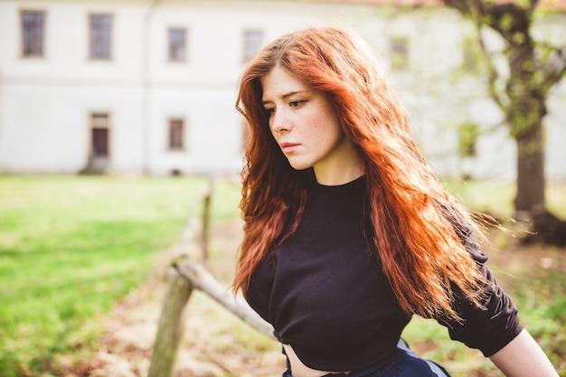 Mooie roodharige jonge vrouw diep in haar gedachten