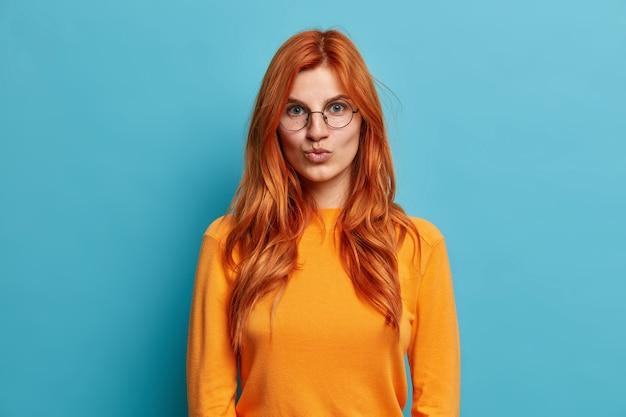 Mooie roodharige jonge vrouw in ronde bril houdt lippen gevouwen wil zoenen iemand gekleed in oranje trui ziet er direct uit.
