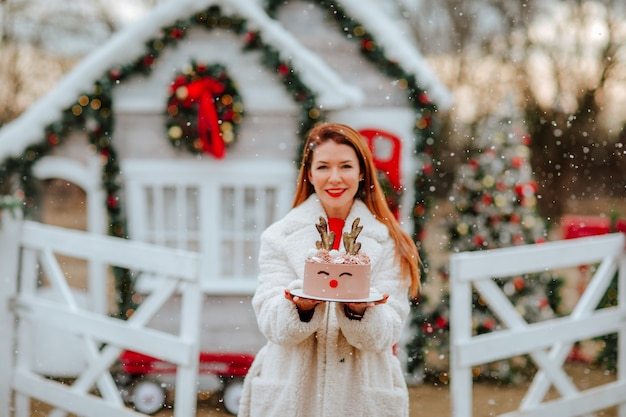 Mooie roodharige jonge vrouw in witte winterjas met zelfgemaakte kerstcake zoals vakantieherten tegen versierd huis en witte omheining. focus ligt op de taart. sneeuwen.