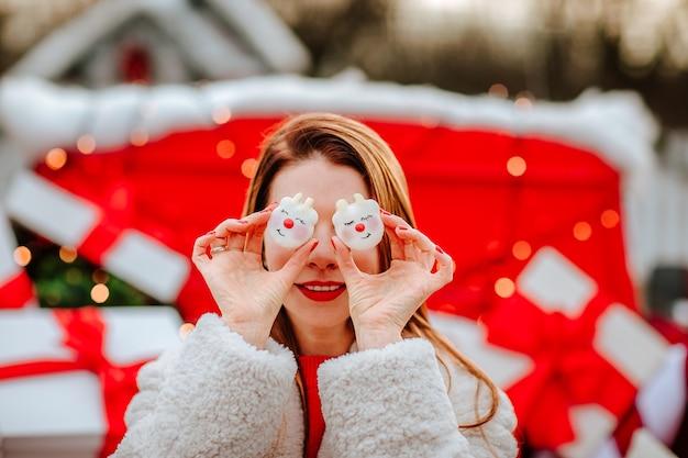 Mooie roodharige jonge vrouw in witte winterjas met zelfgemaakte kerstmakarons voor haar ogen, zittend in een rood versierde auto met cadeautjes. sneeuwen. . de nadruk ligt op bitterkoekjes.