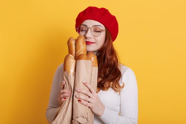Mooie roodharige jonge vrouw met papieren zak met brood op geel