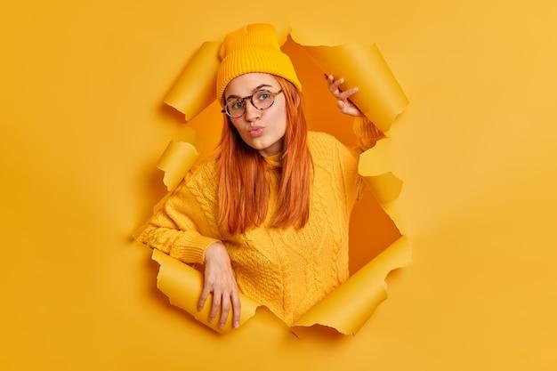 Mooie roodharige jonge vrouw met ronde lippen gekleed in hoed en trui heeft een flirtende uitdrukking gekleed in gele kleding staat door gescheurd papier