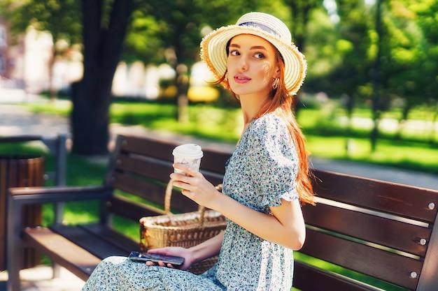 Mooie roodharige jonge vrouw ontspannen op de bank in het stadspark met mobiele telefoon en koffie...