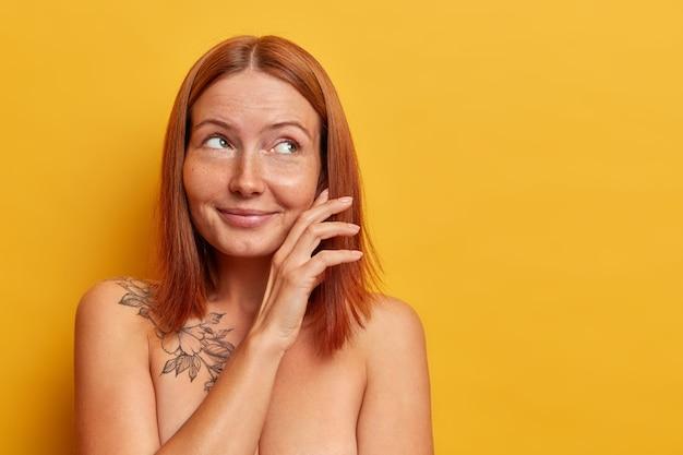 Mooie roodharige jonge vrouw raakt de wang zachtjes aan, kijkt met een dromerige, bedachtzame uitdrukking opzij, staat naakt, heeft een goed verzorgd lichaam en een gezonde huid, modellen tegen gele muur, lege ruimte