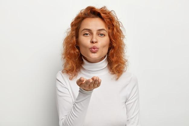 Mooie roodharige krullende jonge vrouw blaast luchtkus naar de camera, maakt mwah, houdt de lippen gevouwen