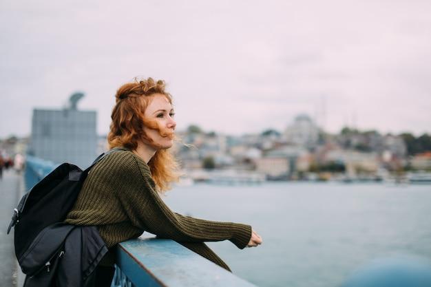 Mooie roodharige krullende meisjesreiziger met een rugzak op de galata-brug in istanboel kijkt in de verte