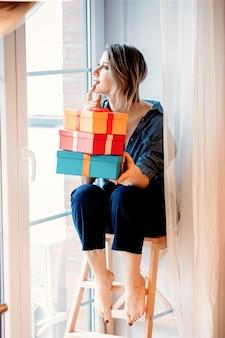 Mooie roodharige meisje met geschenkdoos zittend op kleine trap thuis in de buurt van venster.