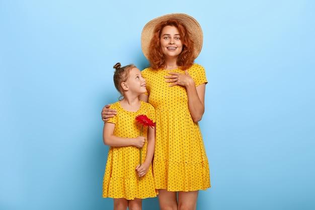 Mooie roodharige moeder en dochter poseren in soortgelijke jurken