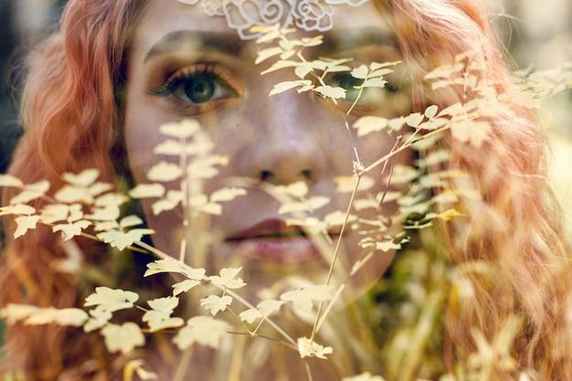 Mooie roodharige noorse vrouw met grote ogen en sproeten op gezicht in het bos. portret van de close-up van de roodharigevrouw in aard, fabelachtig mysterieus uiterlijk lang golvend rood haar