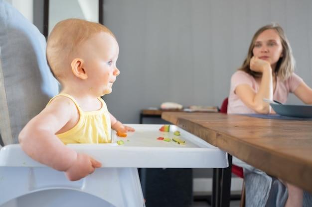 Mooie roodharige pasgeboren eten en zitten in witte plastic babykeukenstoel. mooie jonge moeder zit aan houten tafel en kijkt naar haar kind. familie en jeugdconcept