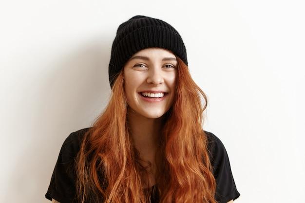 Mooie roodharige tiener die met slordig kapsel en camera kijkt glimlachen