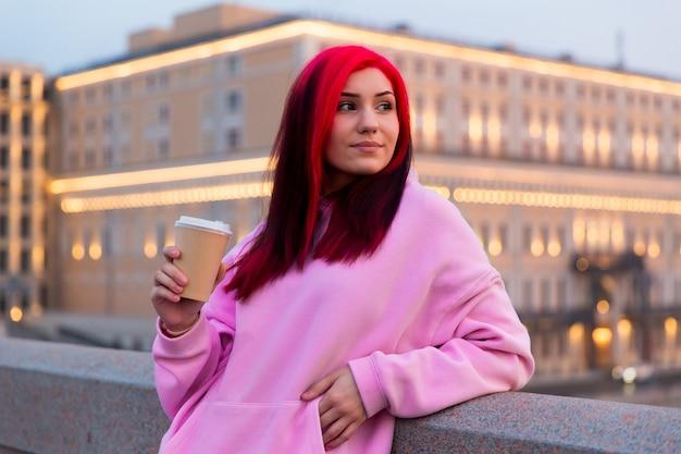 Mooie roodharige tienermeisje in roze hoodie koffie drinken in de avond op verlichte stadsstraat.