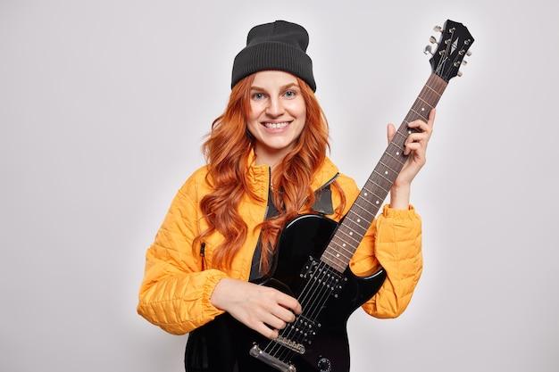 Mooie roodharige tienermeisje leert elektrische gitaar spelen poses met muziekinstrument glimlacht aangenaam popmuzikant draagt trendy hoed oranje jas