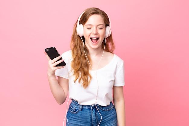 Mooie roodharige vrouw die agressief schreeuwt, erg boos op koptelefoon en smartphone