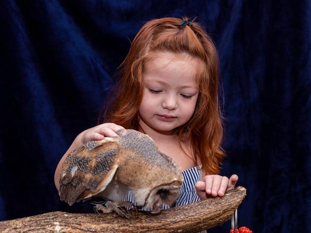 Mooie roodharige vrouw die beeld met haar huisdierenuil neemt