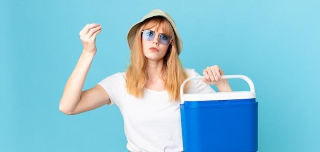 Mooie roodharige vrouw die capice of geldgebaar maakt, zegt dat je moet betalen en een draagbare koelkast vasthoudt. zomer concept