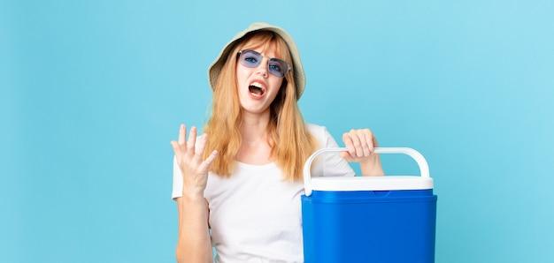 Mooie roodharige vrouw die er wanhopig, gefrustreerd en gestrest uitziet en een draagbare koelkast vasthoudt. zomer concept