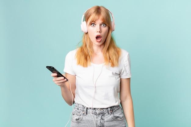 Mooie roodharige vrouw die erg geschokt of verrast kijkt en muziek luistert met een koptelefoon