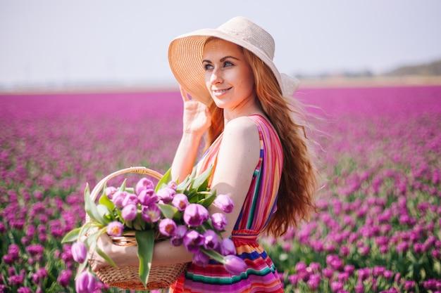 Mooie roodharige vrouw die gestreepte kleding draagt en boeket van tulpenbloemen houdt in mand