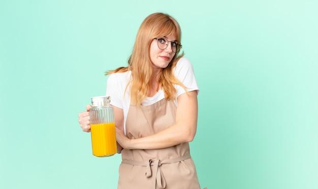 Mooie roodharige vrouw die haar schouders ophaalt, zich verward en onzeker voelt met een schort dat een sinaasappelsap bereidt