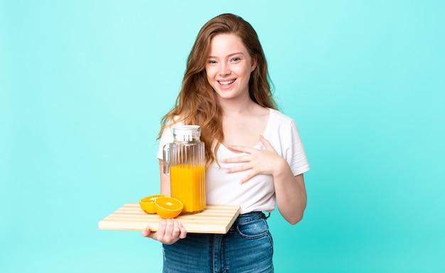 Mooie roodharige vrouw die hardop lacht om een hilarische grap en een sinaasappelsap vasthoudt