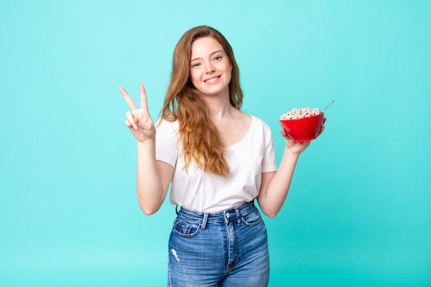 Mooie roodharige vrouw die lacht en er gelukkig uitziet, overwinning of vrede gebaart en een ontbijtkom vasthoudt