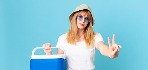 Mooie roodharige vrouw die lacht en er vriendelijk uitziet, nummer twee toont en een draagbare koelkast vasthoudt. zomer concept