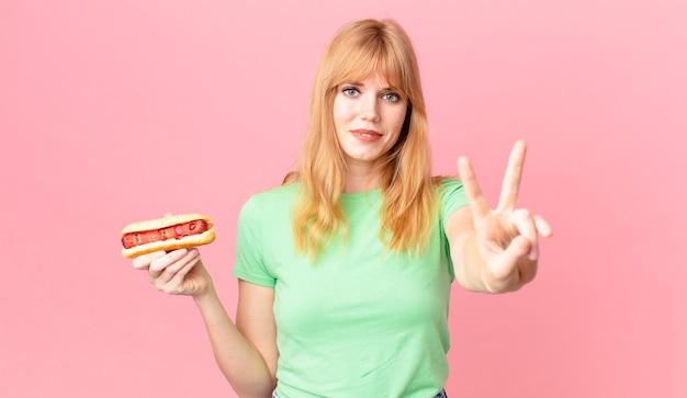 Mooie roodharige vrouw die lacht en er vriendelijk uitziet, nummer twee toont en een hotdog vasthoudt