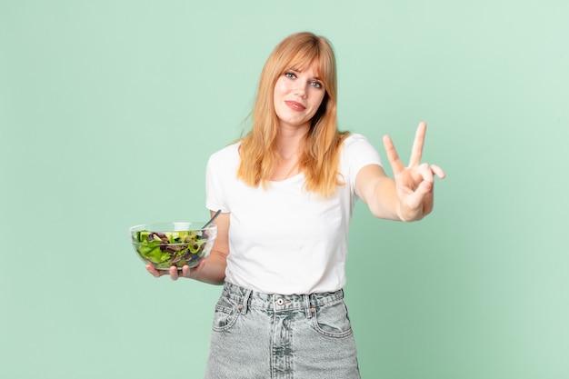 Mooie roodharige vrouw die lacht en er vriendelijk uitziet, nummer twee toont en een salade vasthoudt. dieet concept