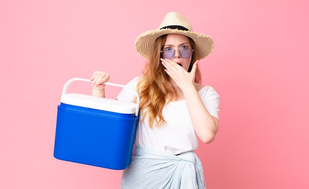 Mooie roodharige vrouw die mond bedekt met handen met een geschokte en een draagbare picknickkoelkast vasthoudt