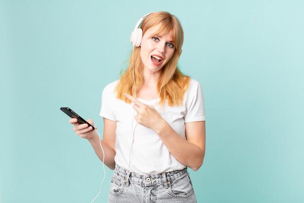 Mooie roodharige vrouw die opgewonden en verrast kijkt en naar de zijkant wijst en muziek luistert met een koptelefoon