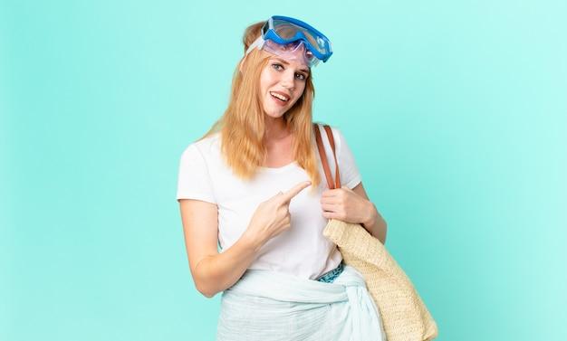 Mooie roodharige vrouw die opgewonden en verrast kijkt en naar de zijkant wijst met een bril. zomer concept